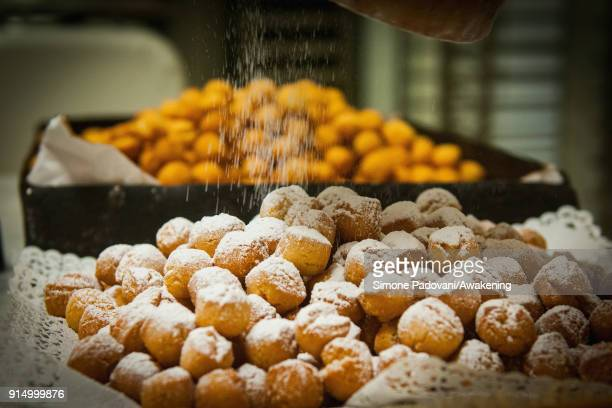 A pastry chef spills sugar over Castagnole a typical sweet of Venetian carnival in Costantini laboratory on February 6 2018 in Venice Italy Galani...