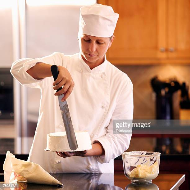 A pastry chef spreads icing on a dessert cake