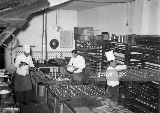 Pastry chefs prepare traditional Yule log cakes for christmas in Paris on December 1938