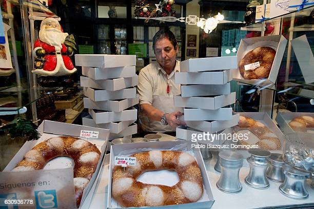A pastry shop seller prepares orders of 'Roscones de Reyes' for customer at the Antigua Pasteleria del Pozo ahead of the Three Kings Day on January 3...