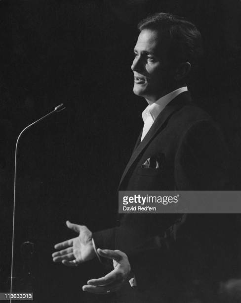 Pat Boone, U.S. Singer, singing into a microphone during a live concert performance in London, England, Great Britain, circa 1960.