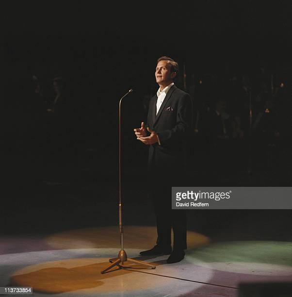 Pat Boone, U.S. Singer, stands singing into a microphone during a live concert performance, circa 1965.