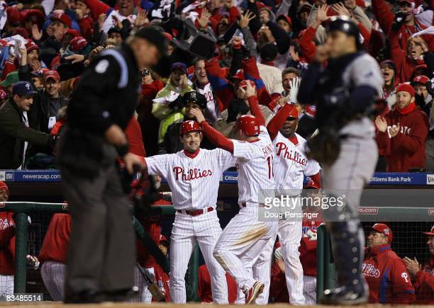 Pat Burrell, Geoff Jenkins and Ryan Howard of the Philadelphia Phillies celebrate after Jenkins scored on a RBI single by Jayson Werth in the bottom...
