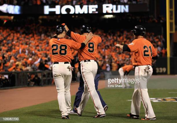 Pat Burrell is congratulated by Buster Posey and Freddy Sanchez of the San Francisco Giants after he hit a three run home run in the first inning...