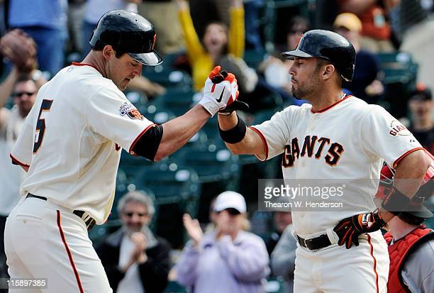 Pat Burrell of the San Francisco Giants is greeted with a high five by teammate Andres Torres after Burrell hit a two run home run in the bottom of...