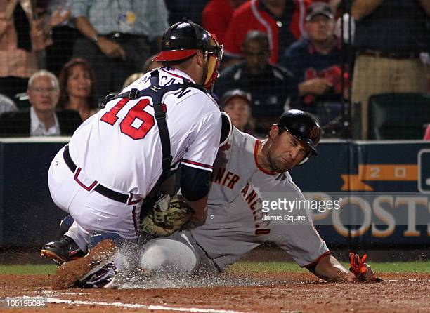 Pat Burrell of the San Francisco Giants is tagged out at home plate while trying to score by Brian McCann of the Atlanta Braves during the 7th inning...