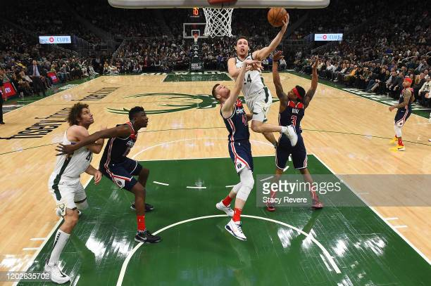 Pat Connaughton of the Milwaukee Bucks drives to the basket against Davis Bertans and Bradley Beal of the Washington Wizards during the second half...