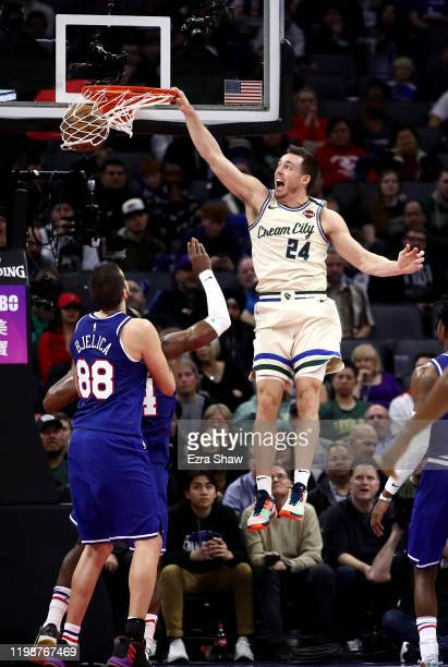 Pat Connaughton of the Milwaukee Bucks dunks over Buddy Hield and Nemanja Bjelica of the Sacramento Kings at Golden 1 Center on January 10 2020 in...