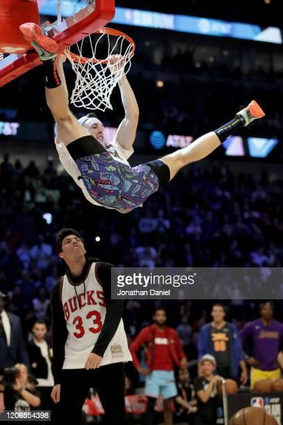 Pat Connaughton of the Milwaukee Bucks dunks the ball over Christian Yelich of the Milwaukee Brewers in the 2020 NBA AllStar ATT Slam Dunk Contest...
