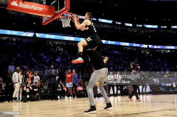 Pat Connaughton of the Milwaukee Bucks dunks the ball over Giannis Antetokounmpo in the 2020 NBA AllStar ATT Slam Dunk Contest during State Farm...
