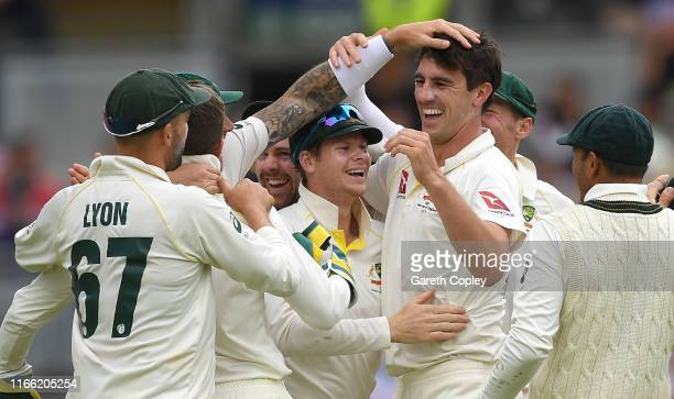 Pat Cummings of Australia celebrates with Steven Smith and teammates after taking the final wicket of Chris Woakes of England to win the 1st...