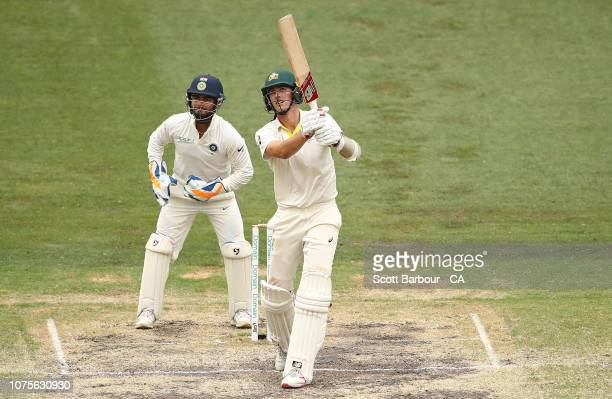 Pat Cummins of Australia bats as wicketkeeper Rishabh Pant of India looks on during day four of the Third Test match in the series between Australia...