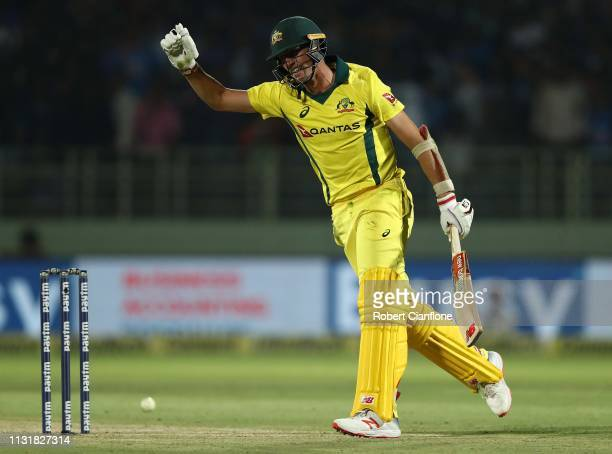 Pat Cummins of Australia celebrates after he scored the winning runs during game one of the T20I Series between India and Australia at ACAVDCA...