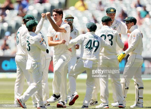Pat Cummins of Australia celebrates after taking the wicket of Prithvi Shaw of India during day three of the First Test match between Australia and...