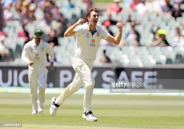 Pat Cummins of Australia celebrates after taking the wicket of Virat Kohli of India during day three of the First Test match between Australia and...
