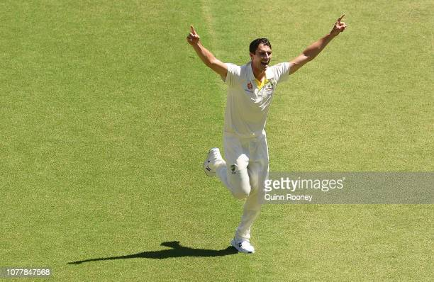 Pat Cummins of Australia celebrates getting the wicket of Virat Kohli of India during day one of the First Test match in the series between Australia...