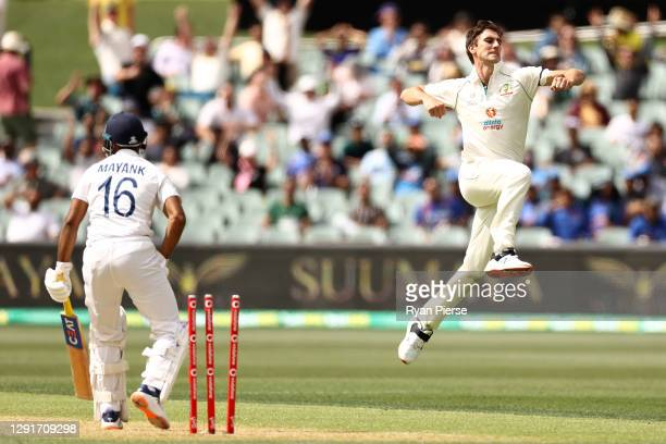 Pat Cummins of Australia celebrates taking the wicket of Mayank Agarwal of India for 17 runs during day one of the First Test match between Australia...