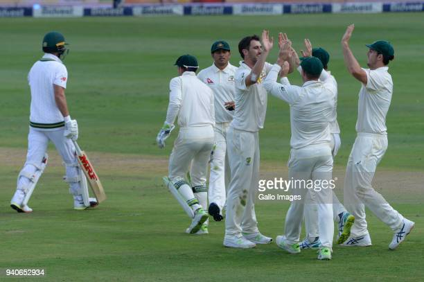 Pat Cummins of Australia celebrates the wicket of AB de Villiers of the Proteas with Tim Paine of Australia with his team mates during day 3 of the...