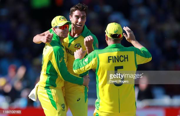 Pat Cummins of Australia celebrates with Steve Smith and Aaron Finch after taking the wicket of Shai Hope during the Group Stage match of the ICC...