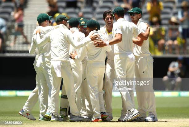 Pat Cummins of Australia celebrates with team mates after taking a catch off his own bowling to dismiss Jasprit Bumrah of India and claim victory...