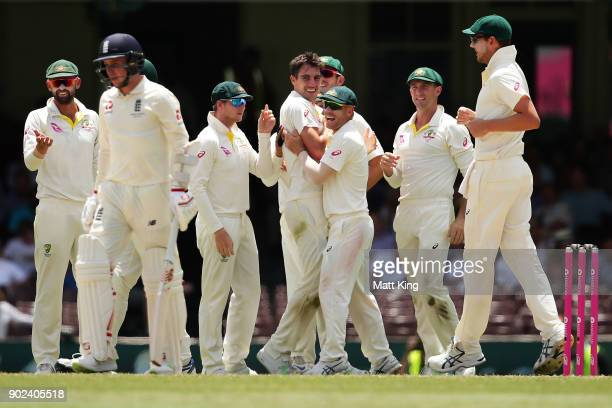 Pat Cummins of Australia celebrates with team mates after taking the wicket of Mason Crane of England during day five of the Fifth Test match in the...
