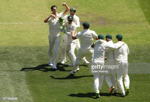 Pat Cummins of Australia is congratulated by team mates after getting the wicket of Virat Kohli of India during day one of the First Test match in...