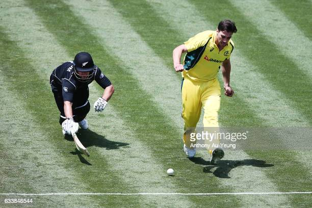 Pat Cummins of Australia kicks the ball towards the stumps in an attempt to run out a dashing Neil Broom of New Zealand during game three of the One...