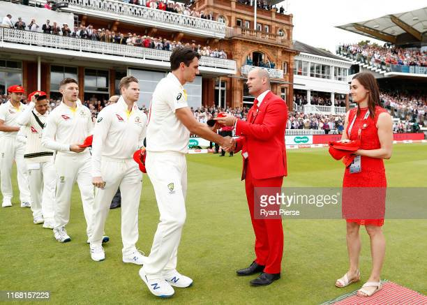 Pat Cummins of Australia presents his red cap to Andrew Strauss on Ruth Strauss Day during day two of the 2nd Specsavers Ashes Test between England...