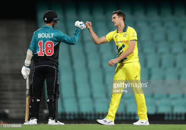 Pat Cummins of Australia taps fists with Trent Boult of New Zealand after taking his final wicket for victory during game one of the One Day...