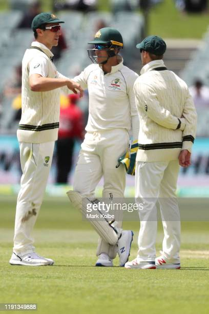 Pat Cummins, Tim Paine and Steve Smith of Australia speak between overs during day four of the Second Test match in the series between Australia and...