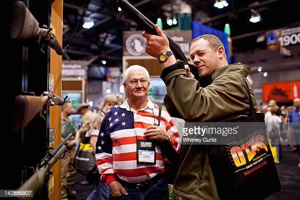 Pat Darling and his nephew Chip Darling look at a Remington rifle display during the NRA Annual Meetings and Exhibits April 14 2012 at America's...