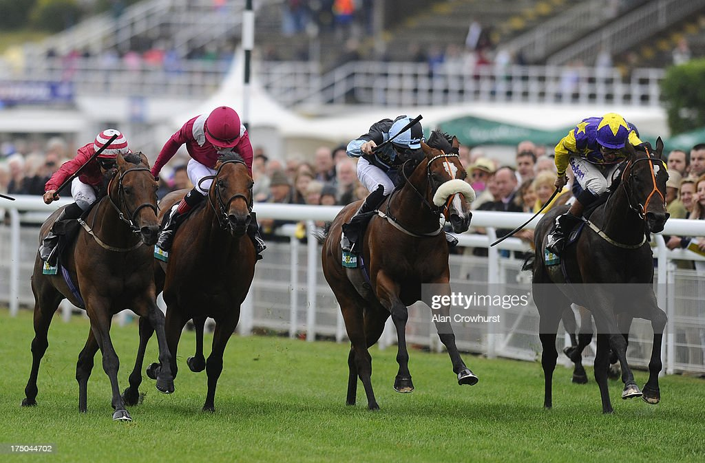 Pat Dobbs riding Brown Sugar (L) on their way to wining The bet365 Molecomb Stakes at Goodwood racecourse on July 30, 2013 in Chichester, England.