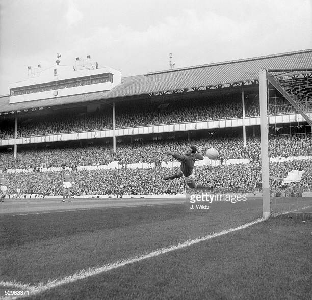 Pat Dunne the Manchester United goalkeeper saves a shot from Jimmy Greaves during a match against Tottenham Hotspur at White Hart Lane 16th October...