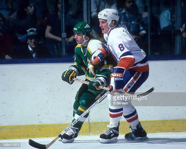 Pat Flatley of the New York Islanders tries to slow down Neal Broten of the Minnesota North Stars during their game on January 29 1985 at the Nassau...
