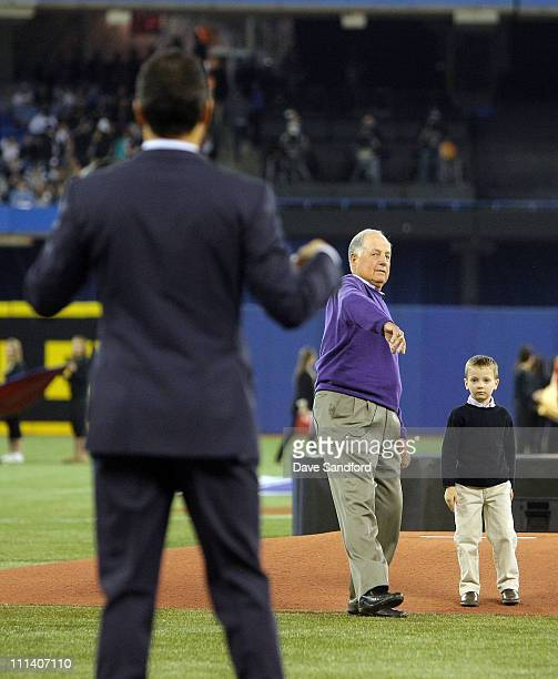 Pat Gillick and grandson Casey Gillick throw the ceremonial pitch to Roberto Alomar before the Toronto Blue Jays play against the Minnesota Twins on...