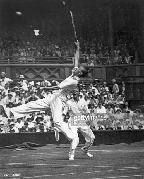 Pat Hughes of Great Britain jumping to make an overhead smash return against Christian Boussus and Antoine Gentien of France as playing partner Fred...