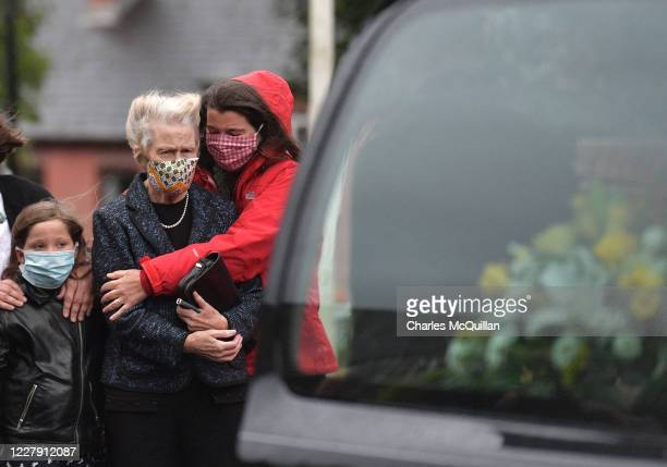 Pat Hume is comforted by family members as the body of her late husband John Humes is brought to St Eugene's Cathedral on August 4, 2020 in...