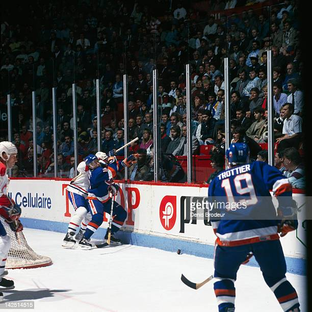 Pat Lafontaine of the New York Islanders gets hit behind the net during a game against the Montreal Cabadiens Circa 1980 at the Montreal Forum in...