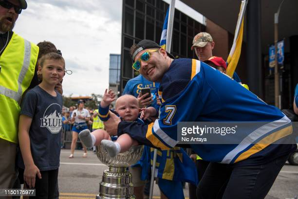 Pat Maroon of the St Louis Blues places a baby in the Stanley Cup during the St Louis Blues Victory Parade and Rally after winning the 2019 Stanley...