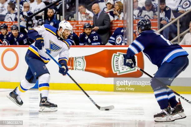 Pat Maroon of the St Louis Blues plays the puck down the ice as Jacob Trouba of the Winnipeg Jets defends during third period action in Game Five of...