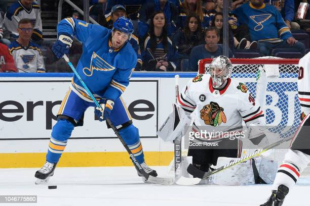 Pat Maroon of the St Louis Blues watches the puck on a shot against Cam Ward of the Chicago Blackhawks at Enterprise Center on October 6 2018 in St...