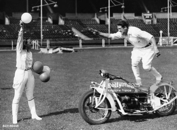 Pat Mossman, acrobate debout sur sa moto qui sera à pleine vitesse pendant son numéro, s'entraîne au tir de ballons tenus par sa femme Helen le 24...