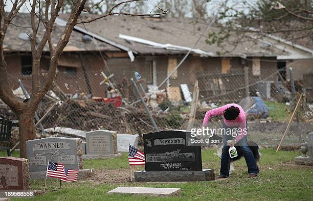 Pat Newcomb cleans debris from around the headstone of her late husband in the Moore City Cemetery on Memorial Day May 27, 2013 in Moore, Oklahoma....