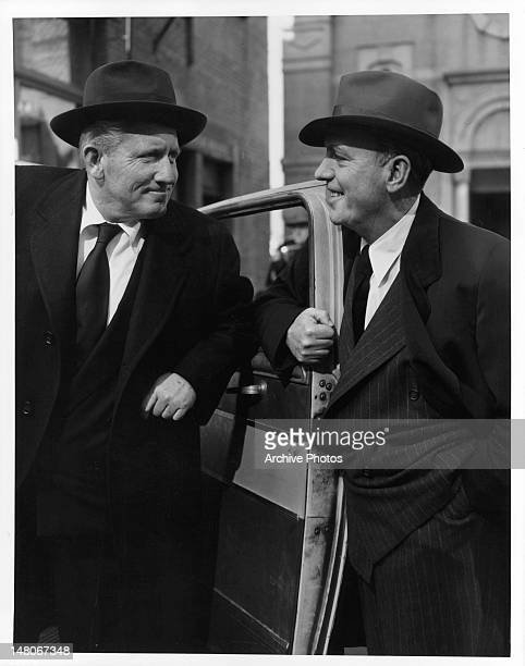 Pat O'Brien holds door open for Spencer Tracy in a scene from the film 'The People Against O'Hara', 1951.