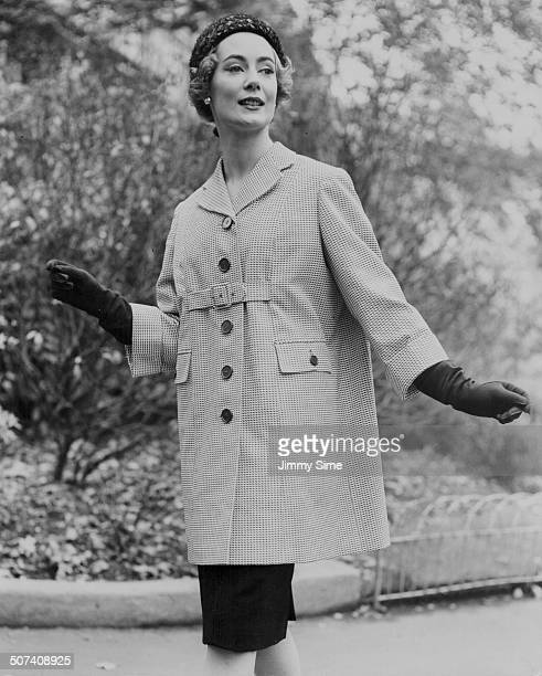Pat O'Reilly models a car coat in navy and white cotton pique, at Burberry's show of rainwear coats at the Savoy Hotel, London, November 4th 1958.
