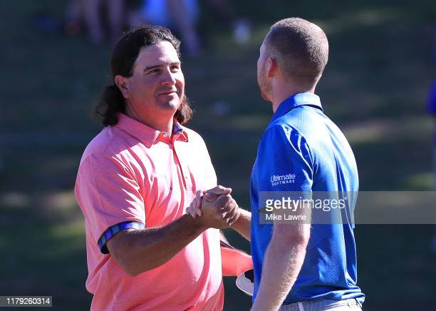 Pat Perez and Daniel Berger shake hands on the 18th green during the third round of the Shriners Hospitals for Children Open at TPC Summerlin on...