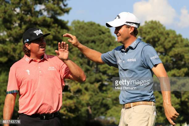 Pat Perez of the United States celebrates his eagle chip in as Kevin Kisner of the United States celebrates his birdie on the 16th green during the...