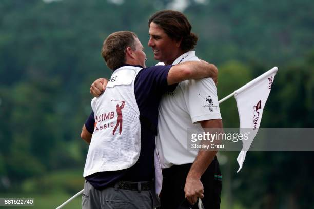 Pat Perez of the United States celebrates with his caddie on the 18th hole after the final round of the 2017 CIMB Classic at TPC Kuala Lumpur on...