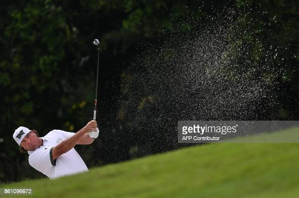 Pat Perez of the US hits the ball out of the bunker on the first fairway during the third round of the 2017 CIMB Classic golf tournament in Kuala...