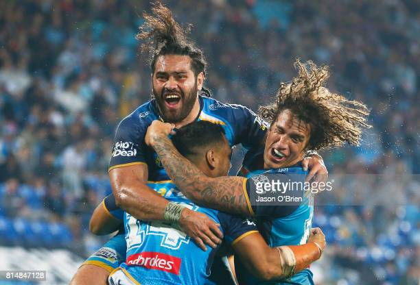 Pat Politoni celebrates a try with Kevin Proctor and Konrad Hurrell during the round 19 NRL match between the Gold Coast Titans and the Cronulla...